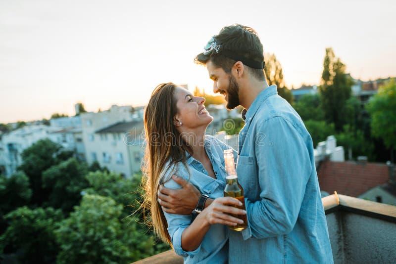 享用饮料和阳台的愉快的夫妇 免版税库存照片