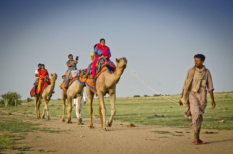 享用骆驼的游人在山姆沙丘乘坐在Jaisalmer,拉贾斯坦,印度附近 免版税库存照片