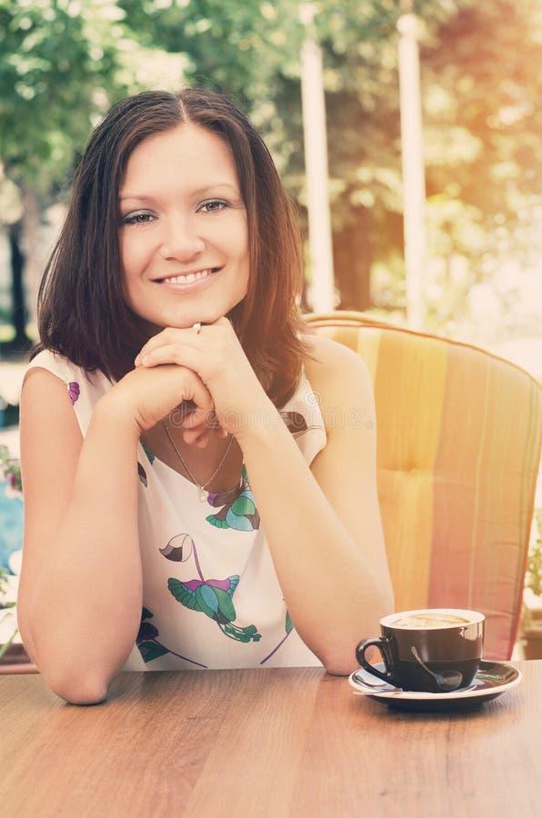 享用capuccino的微笑的夫人 免版税库存图片