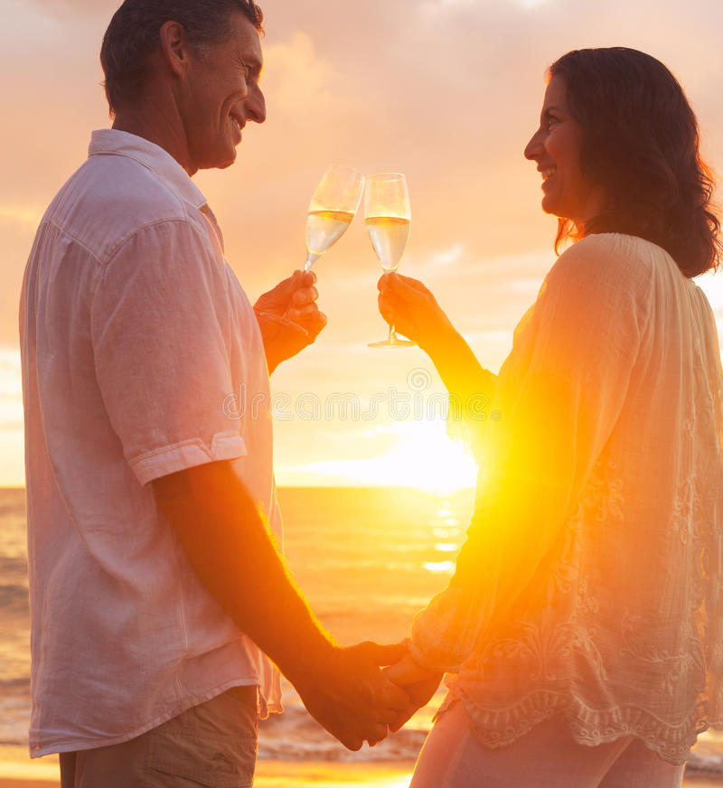 享用Champene的玻璃在海滩的夫妇在日落 免版税库存照片
