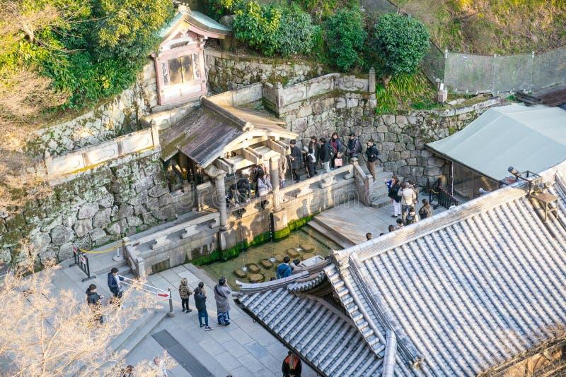 京都,日本- 2018年3月2日:人们等待在行的,从3条圣水线的挖出的水与长的把柄杯子和祈祷的他 免版税库存图片