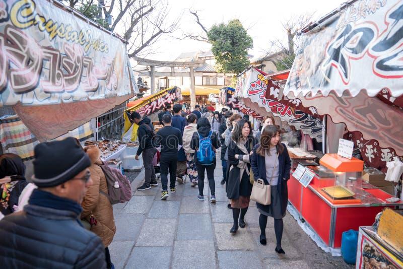 京都,日本- 2018年3月2日:人旅客,小组游览,本地人,日本人走和购物,食物,快餐和 库存图片
