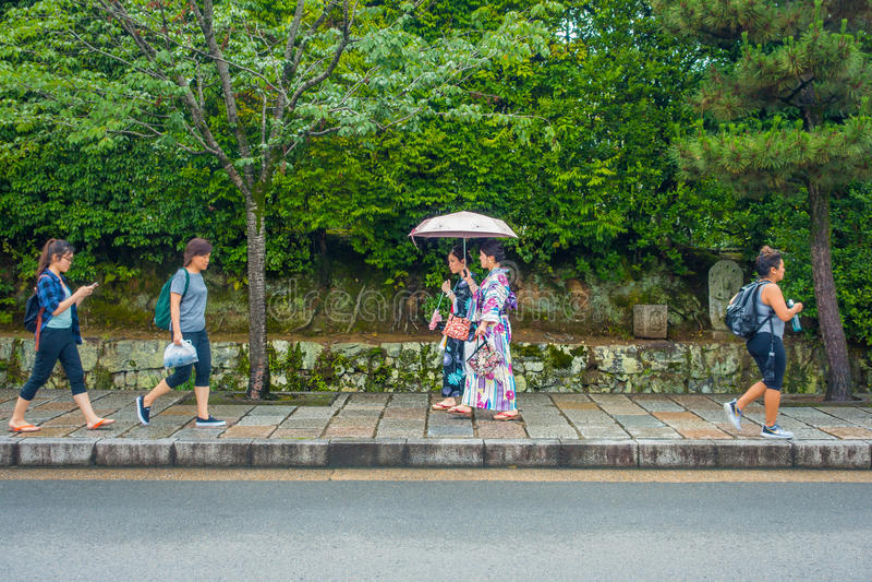 京都,日本- 2017年7月05日:走在道路的未认出的人民在美丽的竹森林在Arashiyama,京都 免版税图库摄影