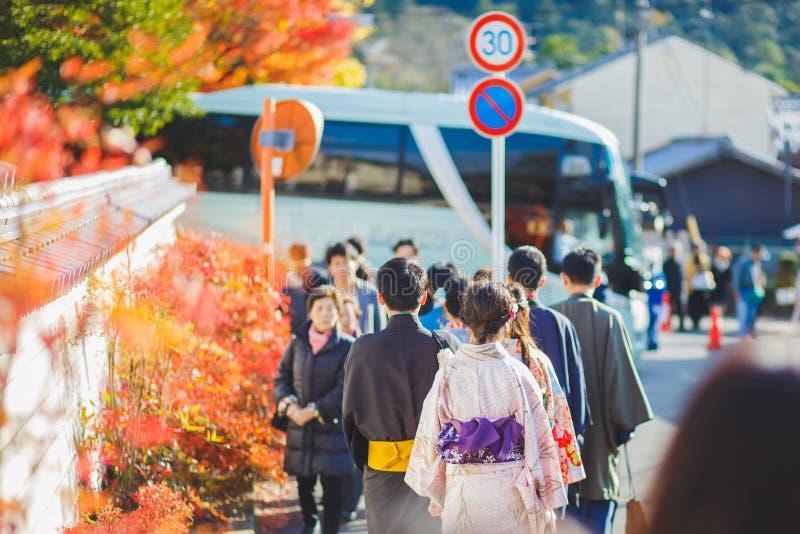 京都,留神yukata和和服的日本- 11月23日, 2016秋天红槭,男人和妇女走在参观Eikando临时雇员的街道上 免版税库存照片