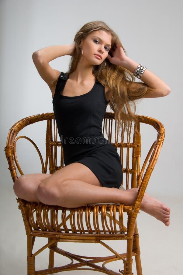 亭亭玉立椅子的女孩 免版税库存照片