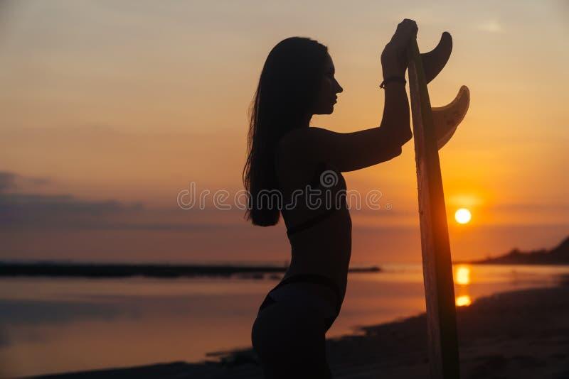 亭亭玉立的女孩剪影有冲浪板的在海滩的手上在美好的日落背景  免版税图库摄影