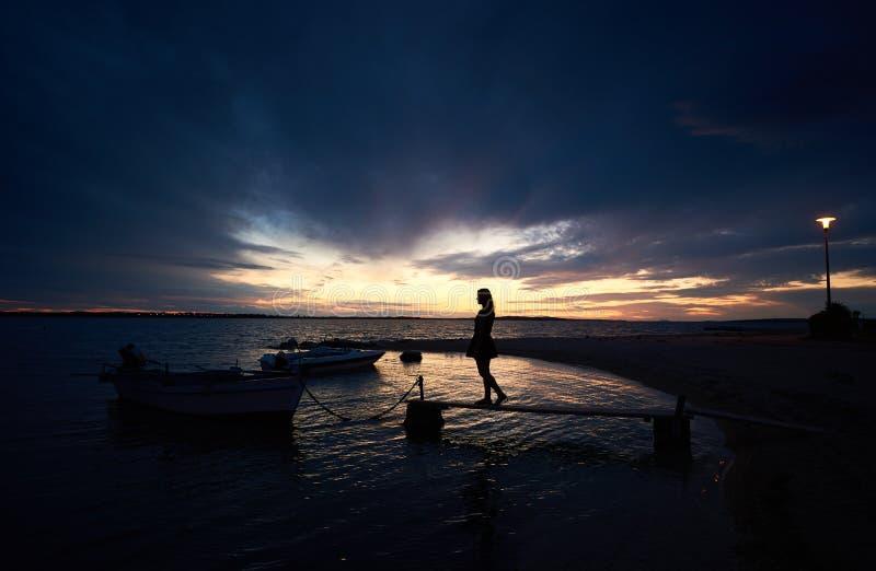 亭亭玉立的女孩身分剪影在狭窄的木桥的在日落的小汽船 库存图片