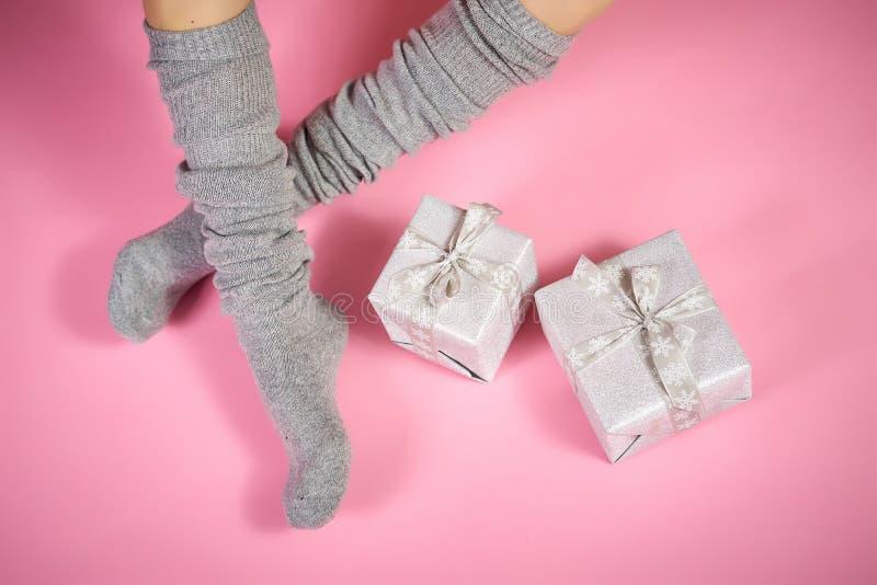 亭亭玉立的女性腿顶视图在温暖的灰色袜子的与在桃红色背景的xmas礼物 免版税库存照片