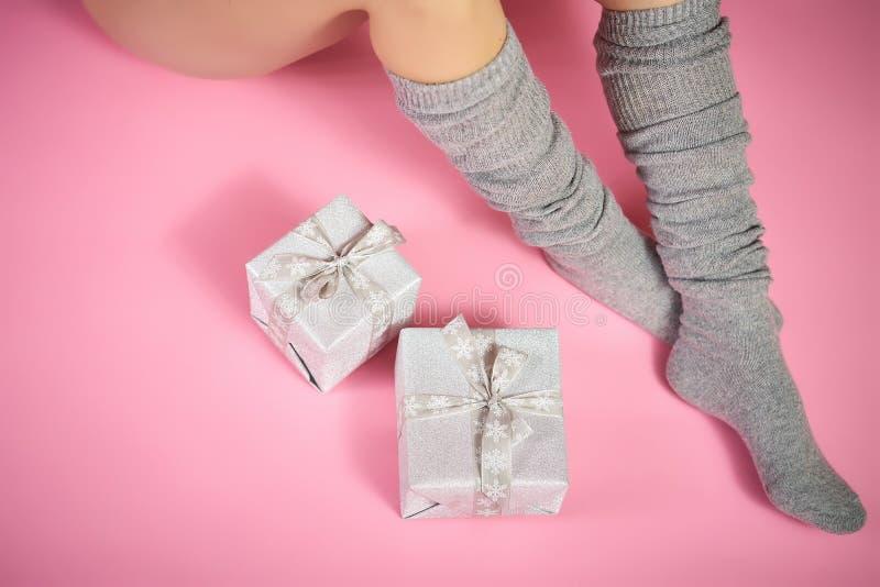 亭亭玉立的女性腿顶视图在温暖的灰色袜子的与在桃红色背景的xmas礼物 免版税库存图片