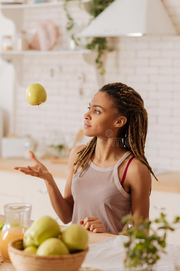 亭亭玉立的妇女佩带的体育顶面投掷的苹果到空气里 库存照片