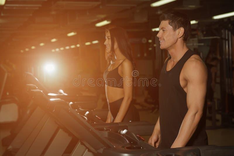 亭亭玉立的妇女和肌肉男性教练员在体育健身房 库存照片