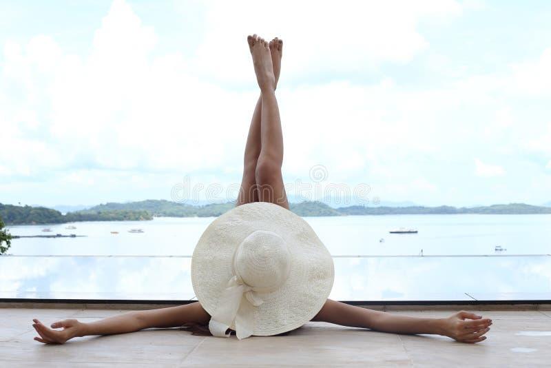 亭亭玉立的妇女在天空中躺下并且提起她的腿与大帽子 库存照片