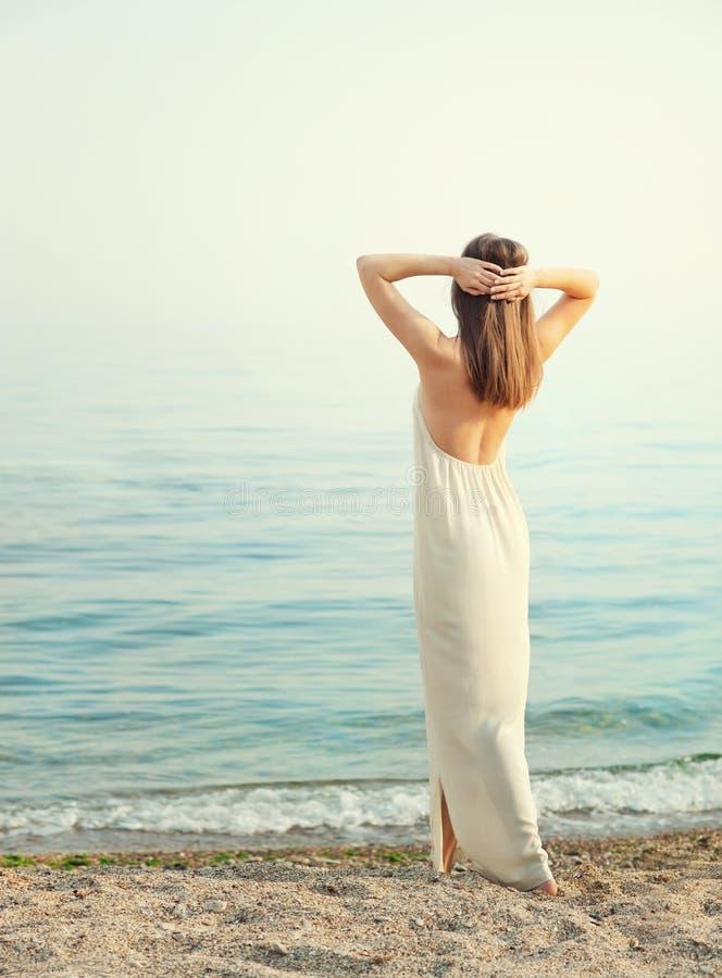 年轻亭亭玉立的妇女在有的长的白色礼服穿戴了开背部,站立用在头后的手 免版税库存照片
