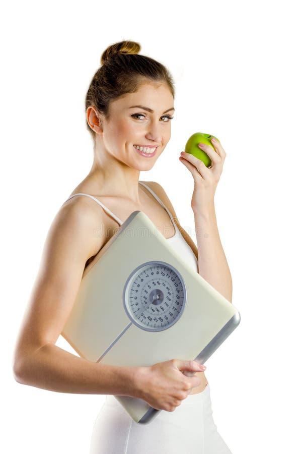亭亭玉立的妇女藏品标度和苹果 免版税库存照片