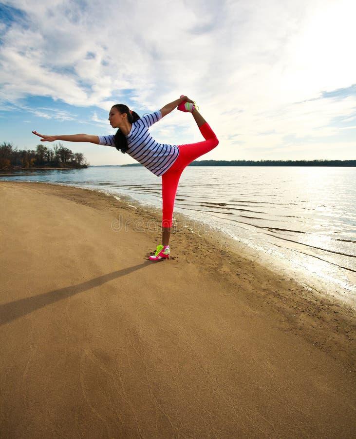 年轻亭亭玉立的妇女,在海滩的锻炼在日出 免版税库存图片