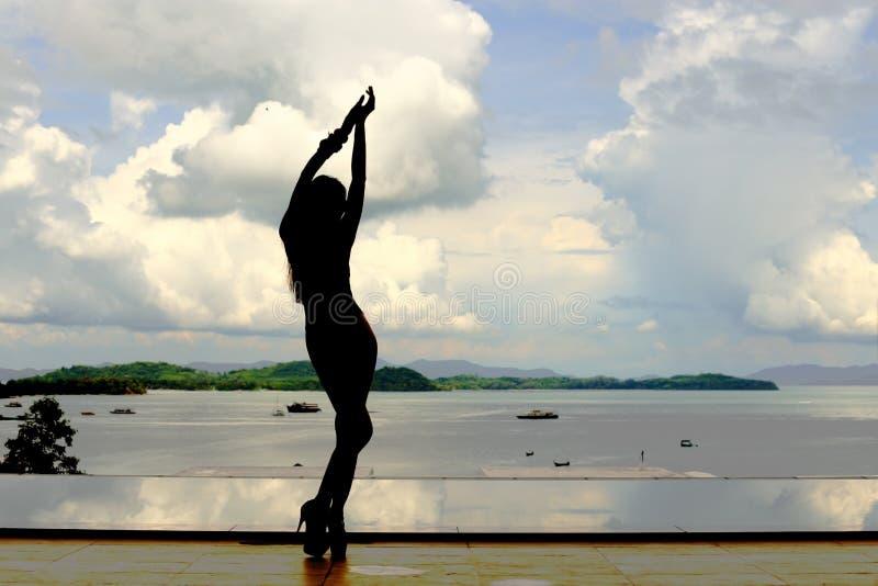 亭亭玉立的形状妇女时尚岗位Silouette在游泳池refl的 库存图片