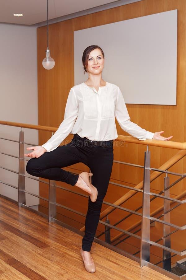 亭亭玉立的思考适合运动的年轻白白种人的女商人画象做瑜伽行使 免版税库存照片