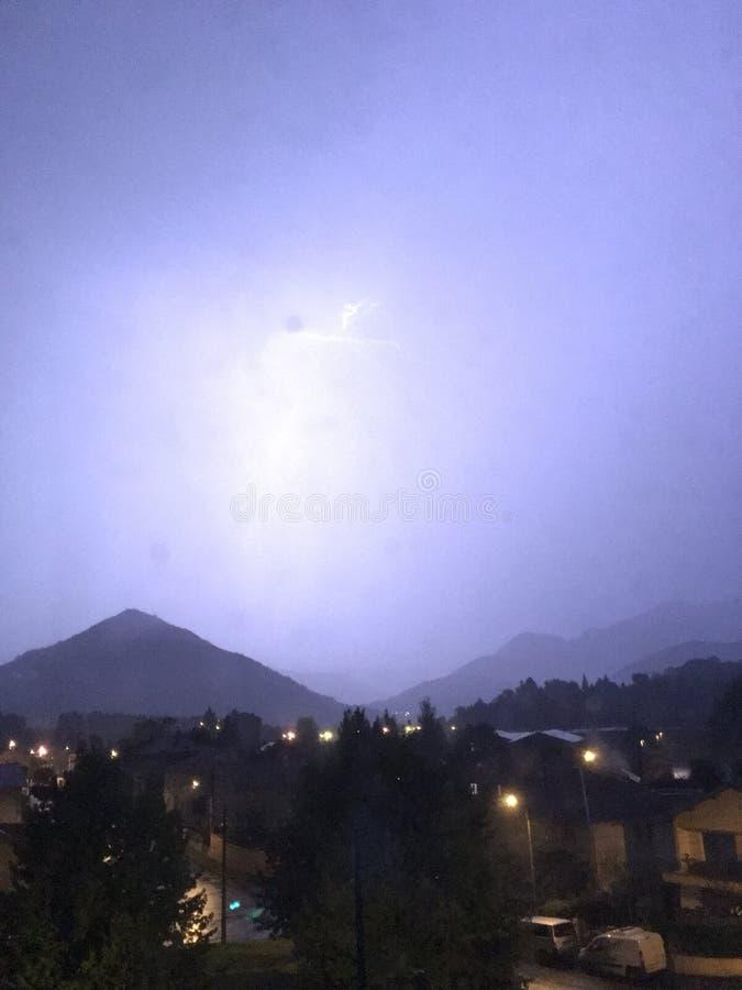 亮光和雷暴在山和城市上 库存照片