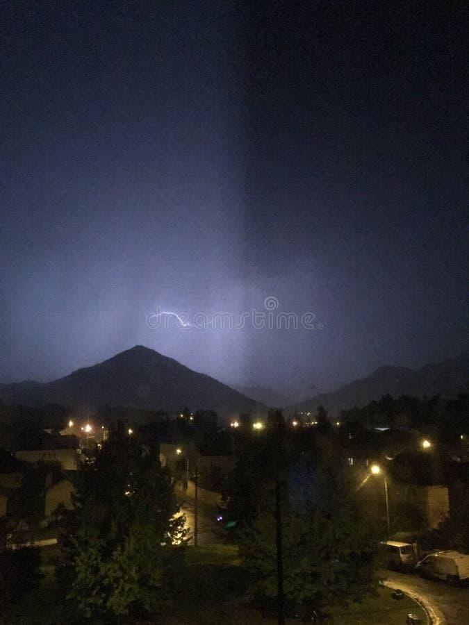 亮光和雷暴在山和城市上 免版税库存图片