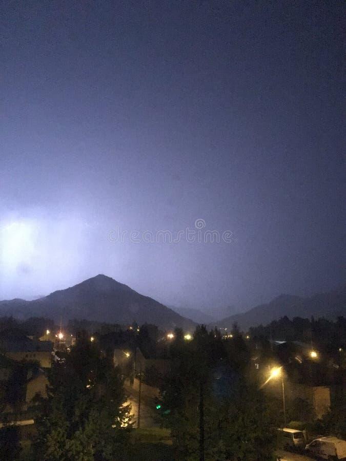 亮光和雷暴在山和城市上 库存图片