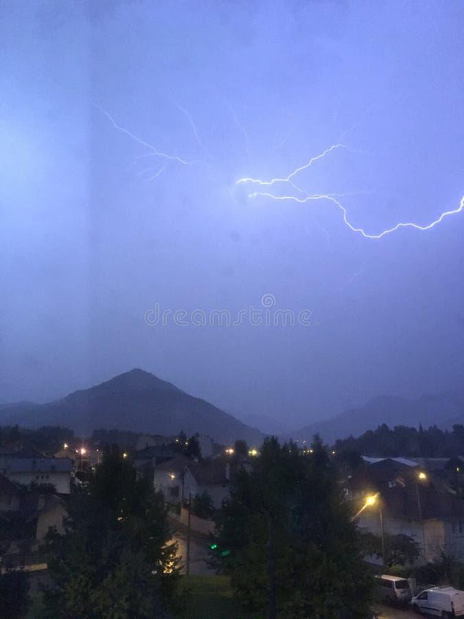 亮光和雷暴在山和城市上 图库摄影