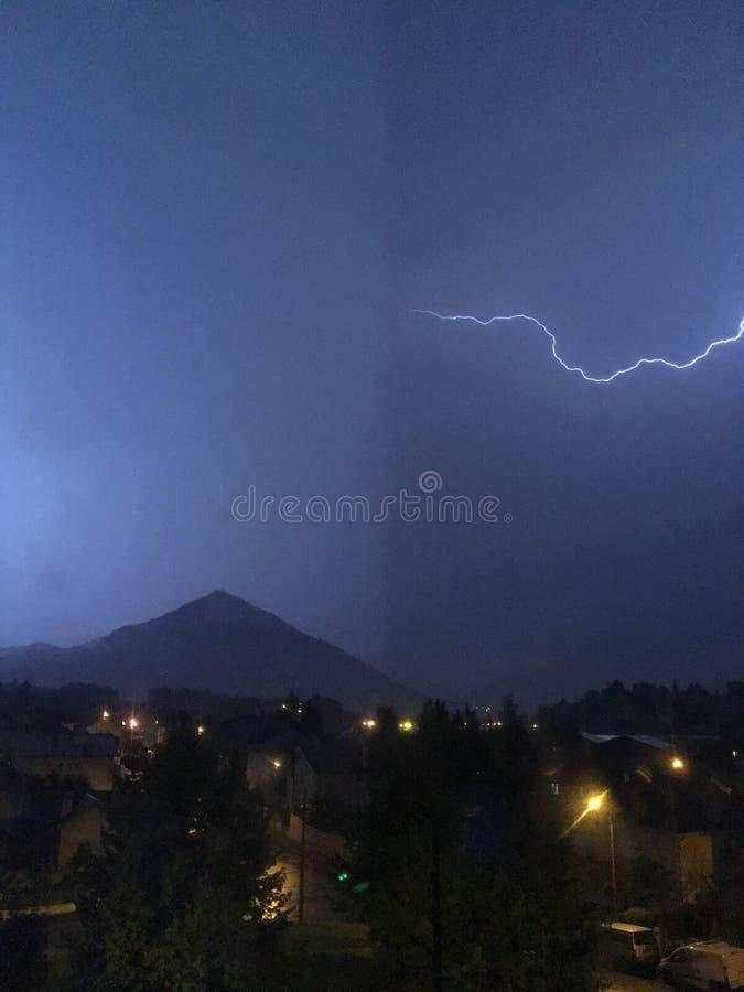 亮光和雷暴在山和城市上 免版税库存照片
