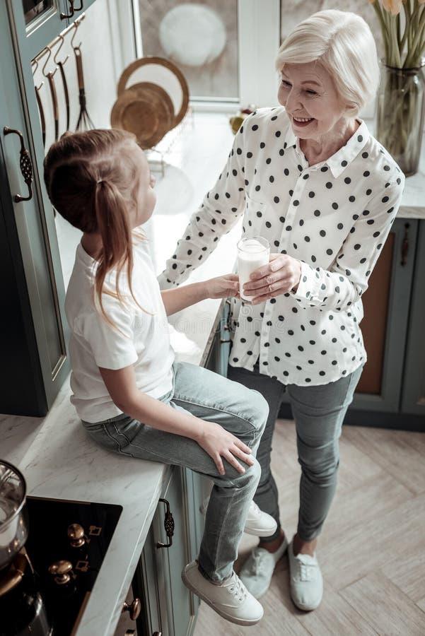 亲切地看她的孙女和提供牛奶的微笑的资深妇女 库存图片
