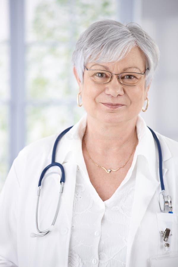 亲切的微笑的女性高级医生纵向  免版税库存照片