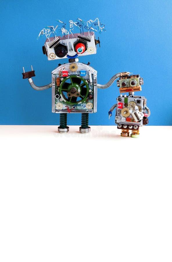 亲切的机器人家庭 妈妈机器人电线发型,插座胳膊 有电灯泡玩具的小孩子靠机械装置维持生命的人 复制空间 免版税库存照片