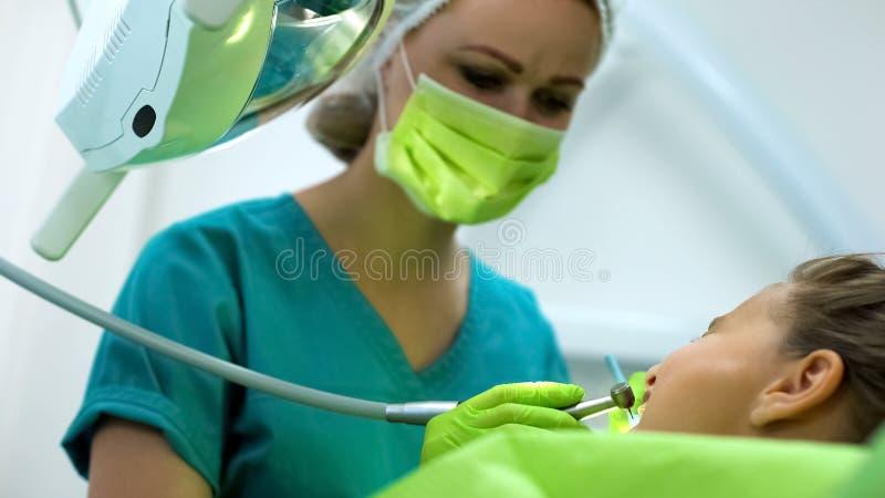 亲切的牙医钻井十几岁的女孩牙,专业小儿科口腔医学 免版税库存照片
