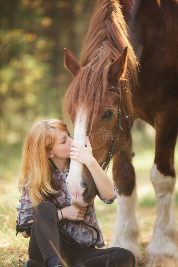 亲吻一匹马的女孩在秋天森林里 库存照片