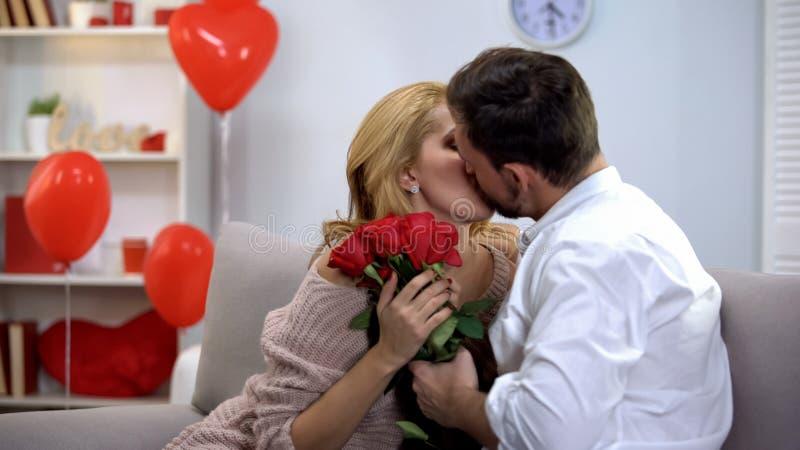 亲吻人的妇女,感恩对花,浪漫惊奇在情人节 库存照片