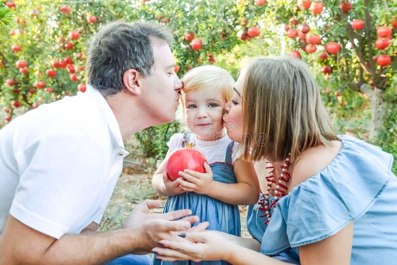 亲吻他们的女婴女儿的愉快的父母画象拿着石榴在日落庭院里结果实 收获的家庭度假 库存照片