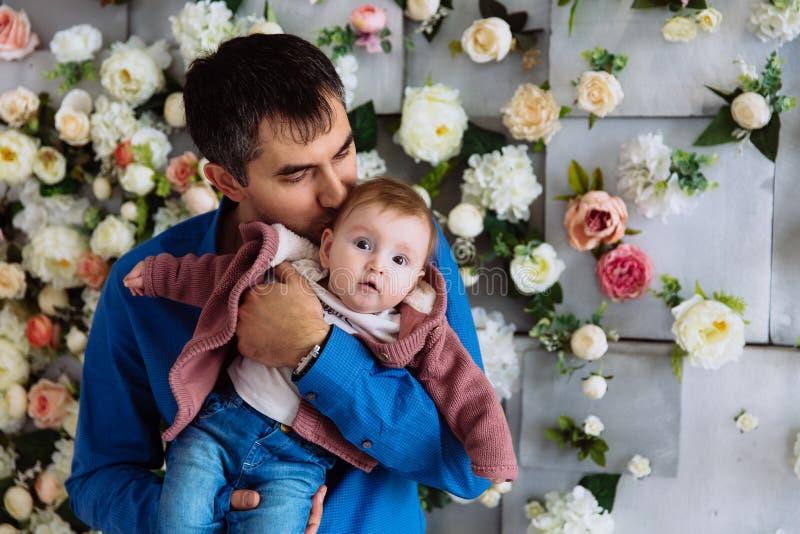 亲吻他的小女儿的一个爱恋的父亲的特写镜头 人成为了父亲并且爱护他的孩子 一个柔和的亲吻 免版税库存图片