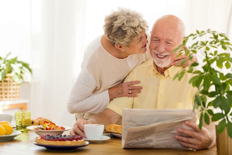亲吻他的微笑的老人读书报纸和他的妻子 免版税库存照片