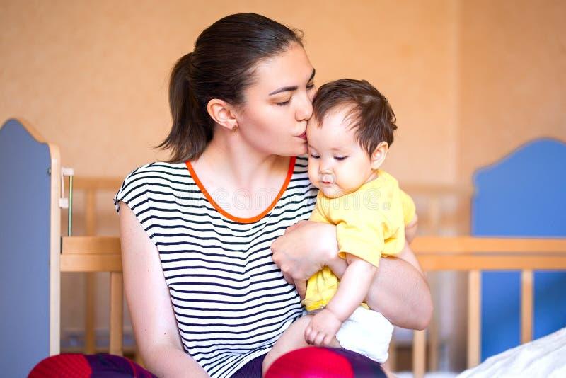 亲吻和纵容她的婴孩的美丽的年轻母亲 混合的族种哈萨克人 图库摄影