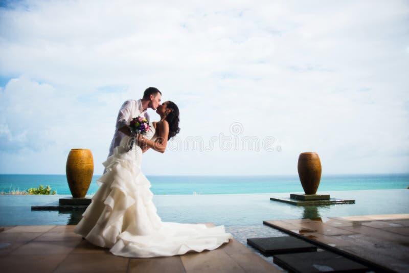 亲吻在一个美丽的热带海滩的一个清楚的晴天的新娘和新郎 库存照片