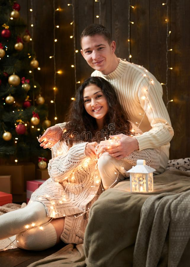亲吻在圣诞灯和装饰的年轻夫妇,穿戴在白色,在黑暗的木背景,浪漫晚上, w的杉树 免版税图库摄影