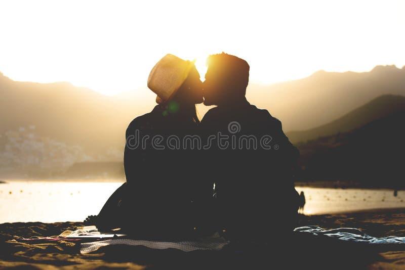 亲吻在日落的海滩-青少年恋人剪影的浪漫年轻夫妇在他们的故事初的坐沙子 免版税库存图片