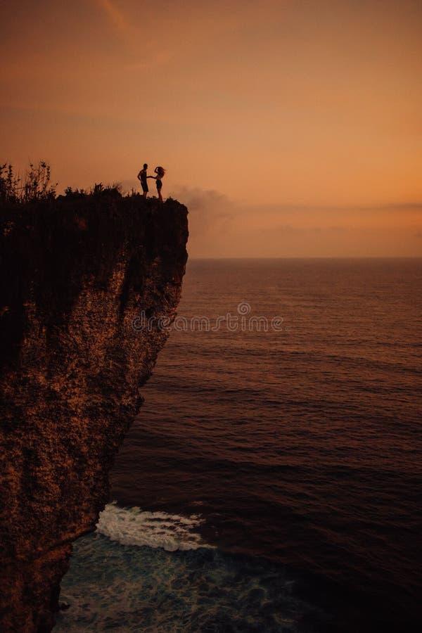 亲吻在日落靠近海,剪影的年轻美好的夫妇 免版税库存照片