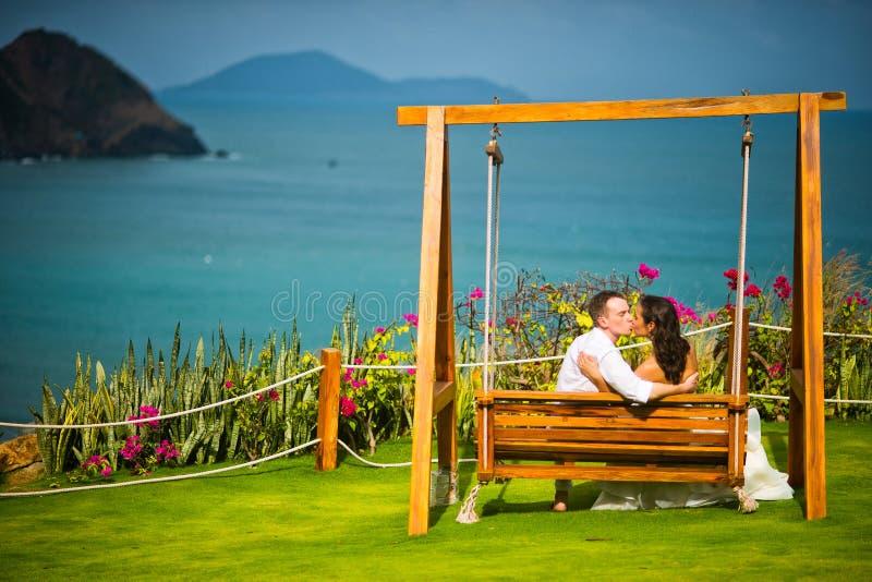 亲吻在海洋和山背景的摇摆的新娘和新郎  免版税库存图片