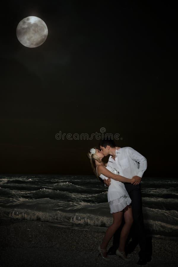 亲吻在海滩的Сouple在月光之下 库存照片