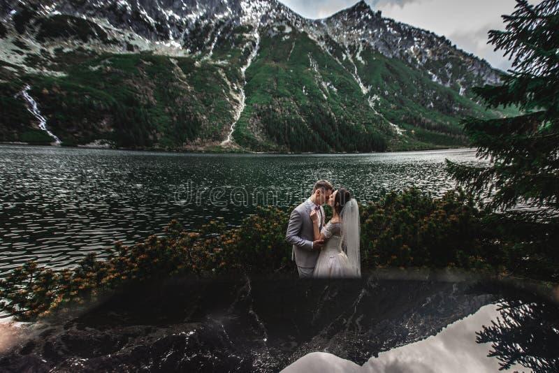 亲吻在湖附近的婚姻的夫妇在太脱拉山在波兰 Morskie Oko 美好的夏日 免版税库存照片