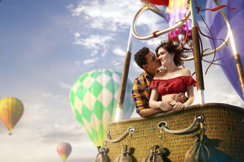 亲吻在热空气气球的年轻美好的不同种族的夫妇 图库摄影