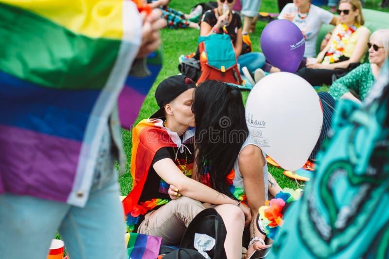 亲吻在赫尔辛基自豪感节日的两个女孩在Kaivopuisto公园 库存图片