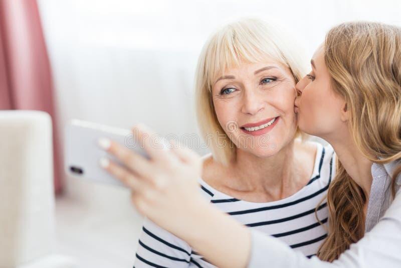 亲吻在面颊母亲的女儿自画象 库存照片