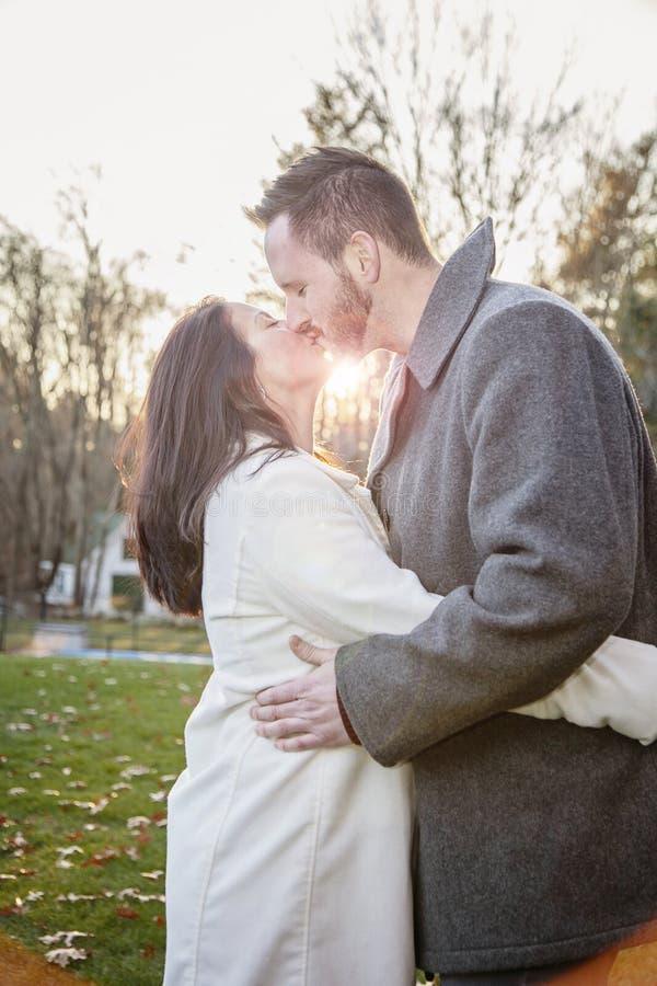 亲吻外面在一冷的秋天天的浪漫年轻夫妇 图库摄影