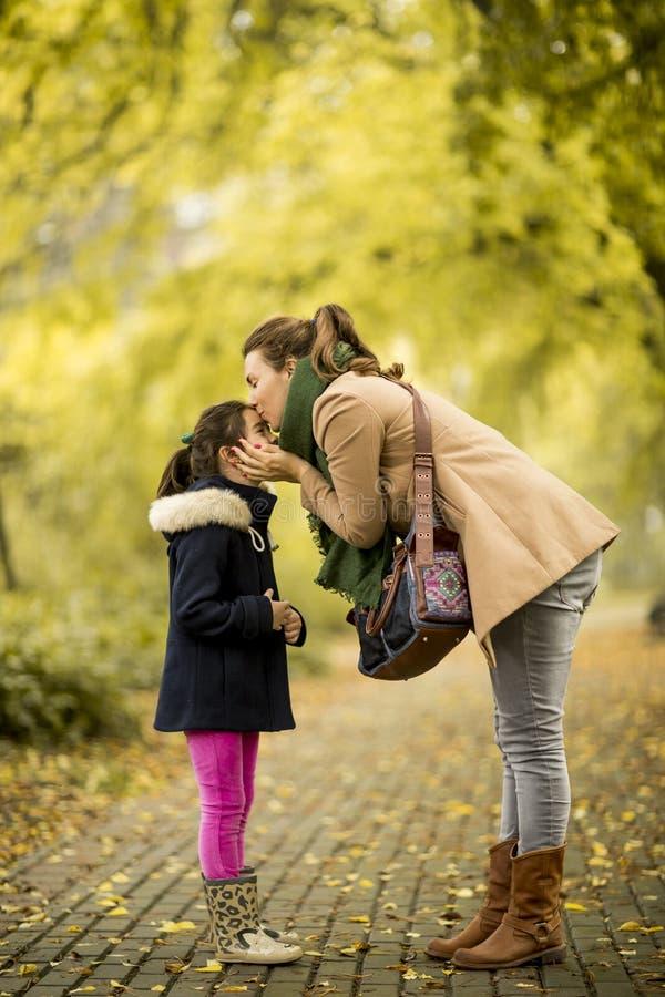 亲吻女儿的母亲在公园 免版税库存图片