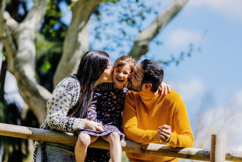 亲吻她可爱的女儿的愉快的父母正面图户外在公园在一好日子 免版税库存照片