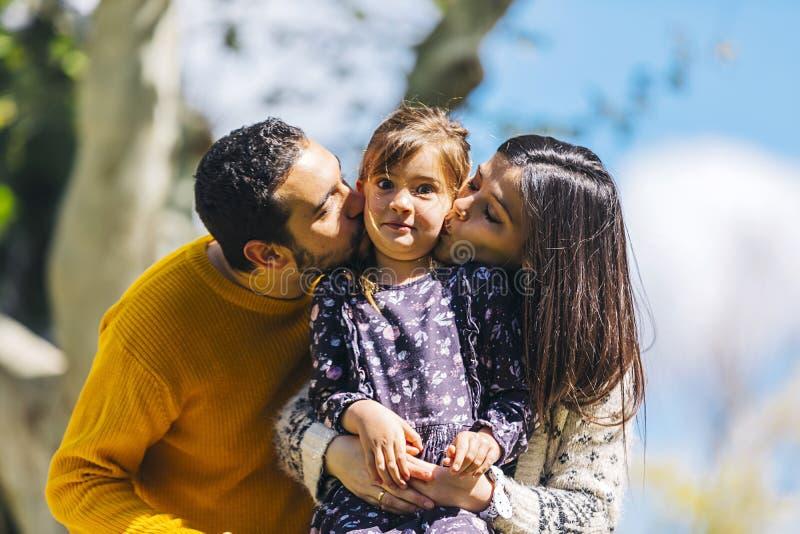 亲吻她可爱的女儿的愉快的父母正面图户外在公园在一好日子 库存图片